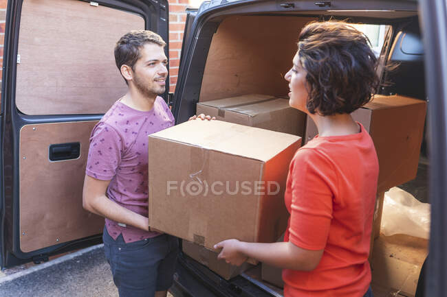 Пара розвантажити картонні коробки з фургона. — стокове фото
