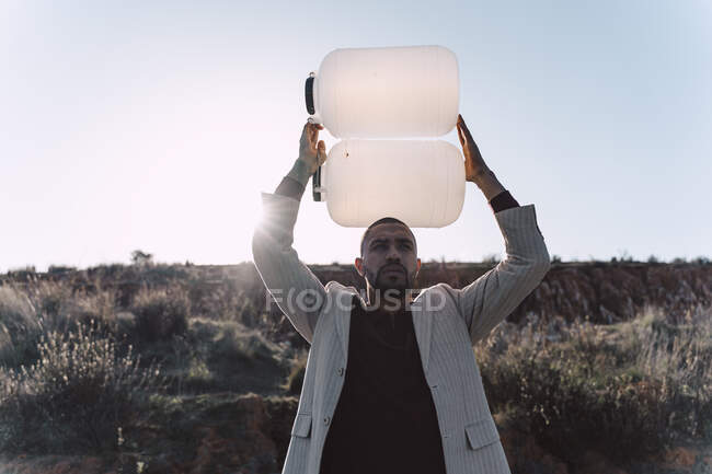 Young man holding empty water can in barren land — Stock Photo