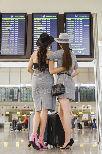 Two fashionable young women at the airport terminal checking the arrival departure board — Stock Photo