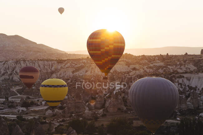 Colorful hot air balloons flying over rocky landscape in Goreme during sunset, Cappadocia, Turkey — Stock Photo