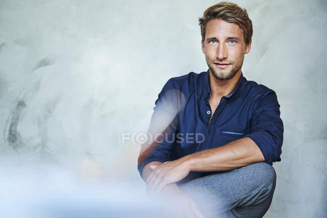 Retrato de un joven confiado sentado - foto de stock