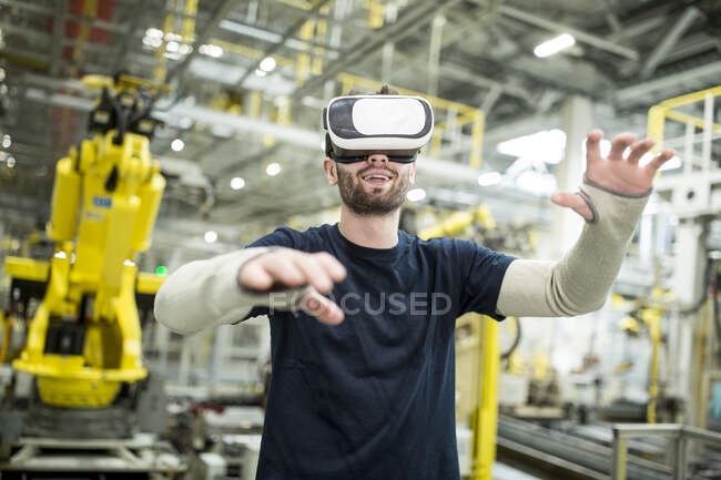 Man wearing VR glasses in modern factory — Stock Photo