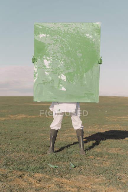 Молода жінка ховається за зеленим малюнком на сухому полі. — стокове фото