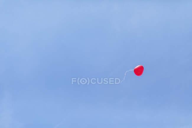 Під час весільної церемонії на небі над блакитним небом летить куля червоної серцевої форми. — стокове фото