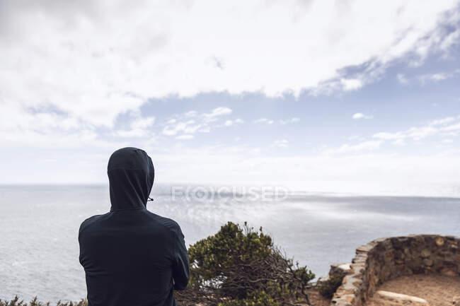 Вид сзади на человека в куртке с капюшоном, смотрящего на море, Кейп-Пойнт, Западная Мыса, Южная Африка — стоковое фото