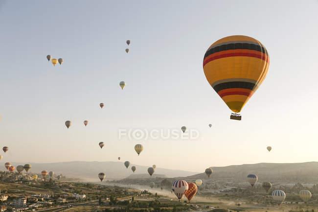 Coloridos globos de aire caliente volando sobre tierra en el Parque Nacional Goreme, Capadocia, Turquía - foto de stock