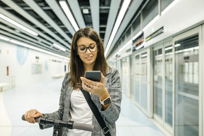 Young businesswoman with e-scooter using the phone at the subway station — Stock Photo