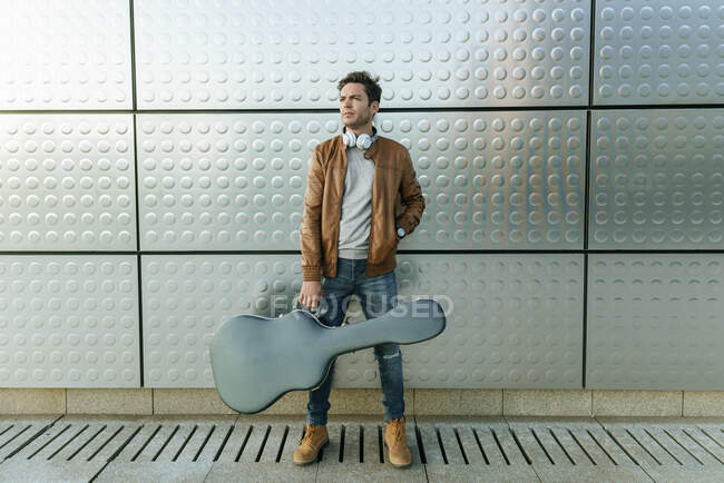 Man with guitar standing in front of a silver wall — Stock Photo