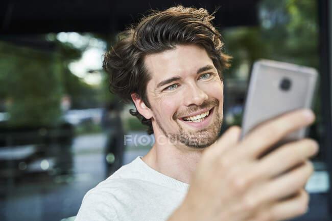 Ritratto di uomo felice che tiene il cellulare in città — Foto stock