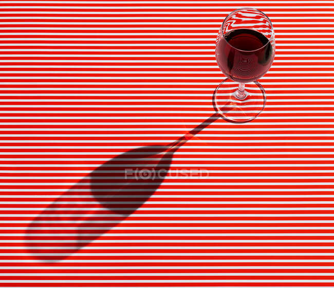 High angle view of red wine served on striped table — Stock Photo