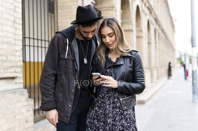 Pareja joven usando smartphone en la ciudad - foto de stock