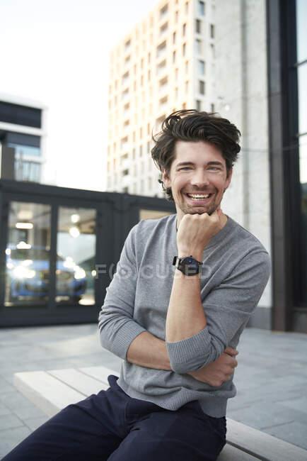 Портрет щасливого чоловіка у сірій сорочці сидить на лавці в місті. — стокове фото