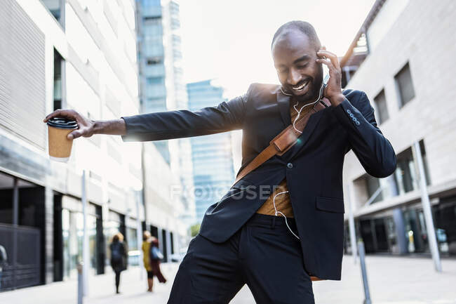 Portrait de jeune homme d'affaires heureux dansant dans la rue tout en écoutant de la musique avec des écouteurs — Photo de stock