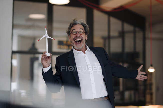 Excited senior businessman with wind turbine model in office — Stock Photo