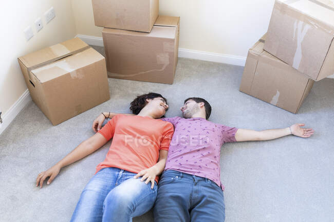 Happy couple moving into new home lying on the carpet floor — Stock Photo