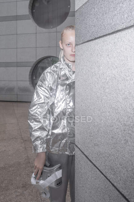 Chica en traje de plata mirando desde detrás de la pared - foto de stock