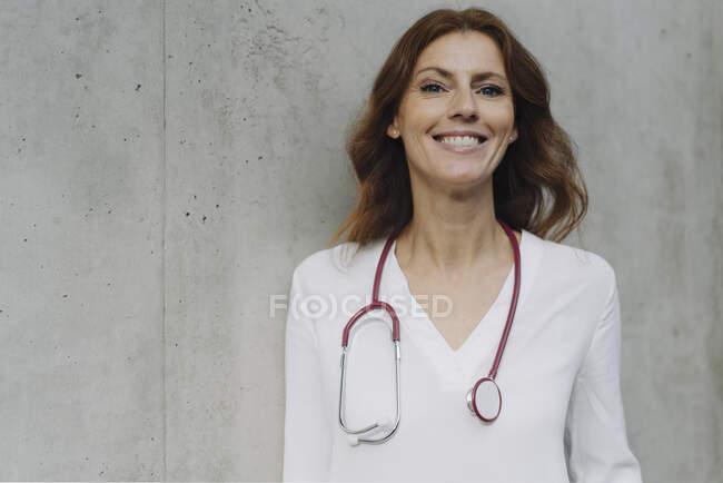 Retrato de una doctora sonriente en una pared de hormigón - foto de stock