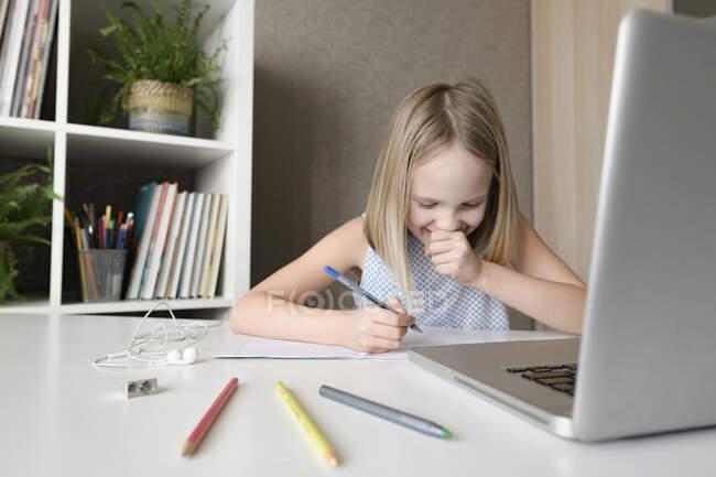 Rindo menina sentada à mesa em casa fazendo lição de casa e usando laptop — Fotografia de Stock