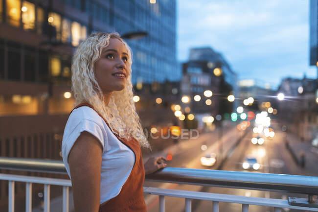 Молода жінка в місті в сутінках з міською вулицею в Лондоні. — стокове фото