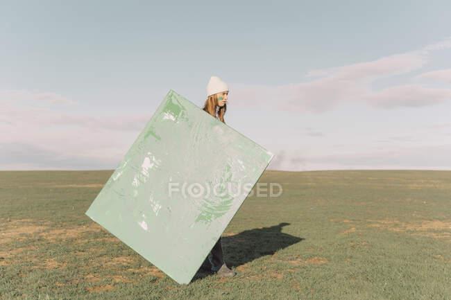 Молода жінка тримає зелене полотно на сухому полі. — стокове фото