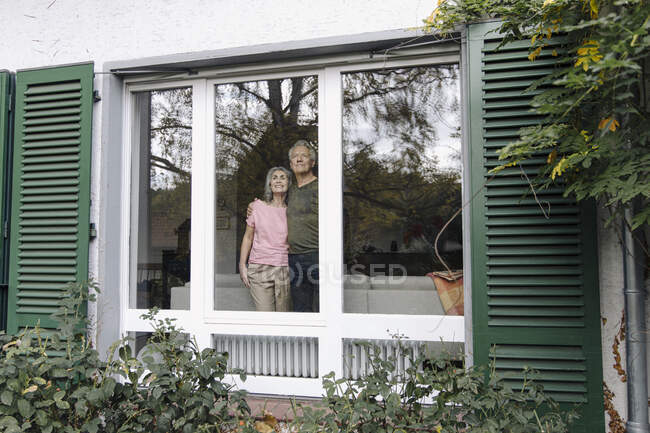 Senior couple behind windowpane of their home looking out — Stock Photo