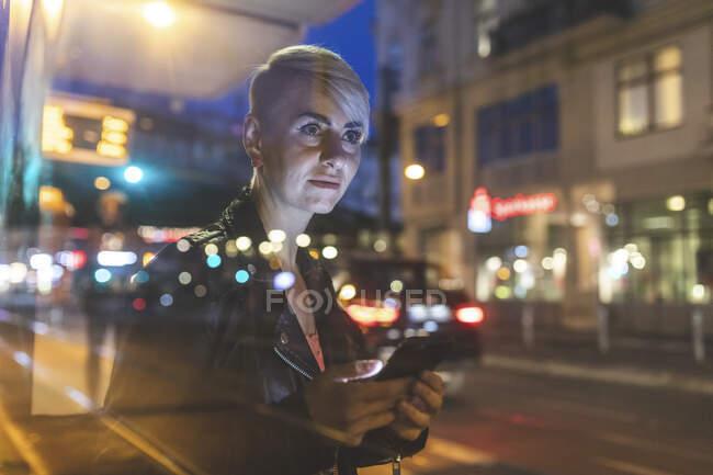 Retrato de mulher loira na parada de bonde à noite usando telefone celular, Berlim, Alemanha — Fotografia de Stock