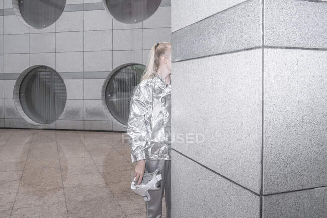 Chica en traje de plata de pie desde detrás de la pared - foto de stock