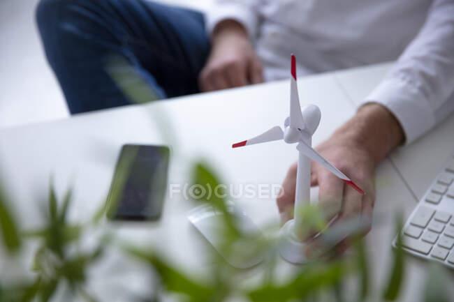 Primer plano del hombre con la mano en el modelo de turbina eólica en la mesa - foto de stock