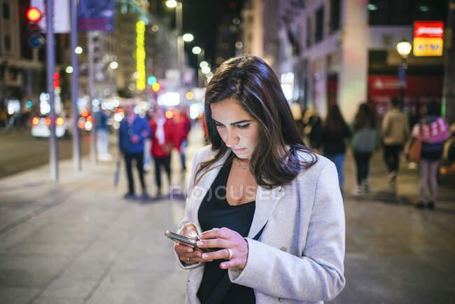 Жінка вночі користується своїм смартфоном. — стокове фото