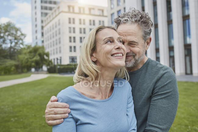 Feliz pareja adulta abrazándose en la ciudad - foto de stock