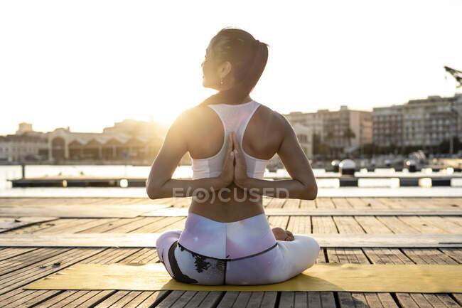 Задний вид азиатки, практикующей йогу на пирсе в гавани вечером — стоковое фото