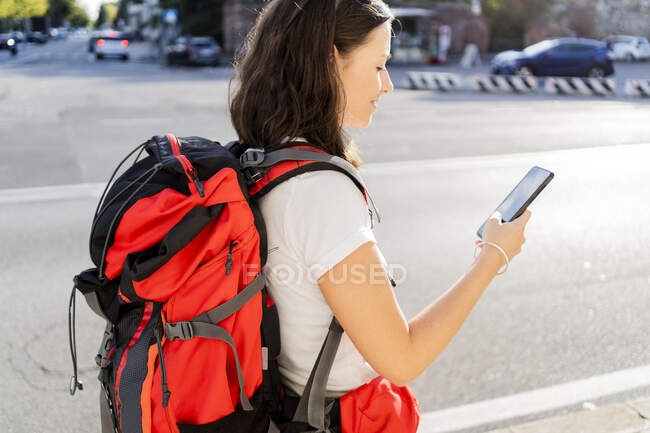 Young female backpacker with red backpack using smartphone in the city, Verona, Italy — Stock Photo