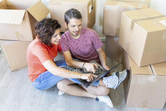 Happy couple moving into new home using laptop — Stock Photo