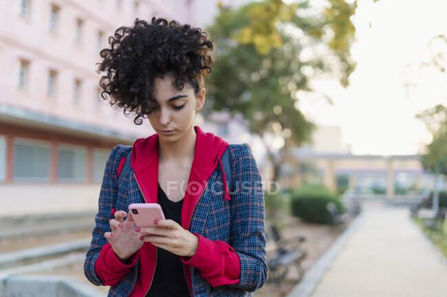 Портрет молодої жінки, яка користується мобільним телефоном на вулиці — стокове фото