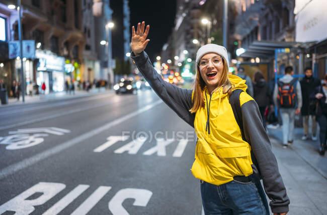 Молода жінка в місті, яка вестиме таксі вночі. — стокове фото