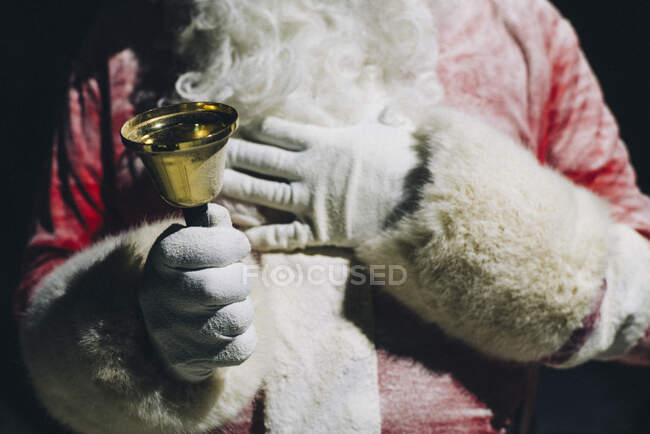 Рука Санта Клауса Holdinmg handbell, close-up — стокове фото