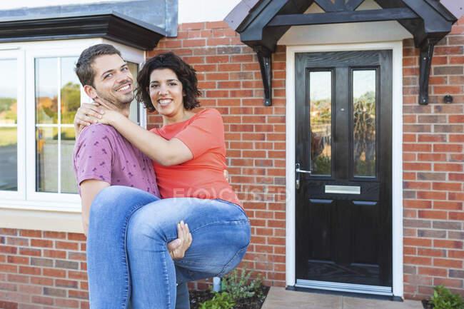 Homem feliz carregando mulher na frente de sua nova casa — Fotografia de Stock