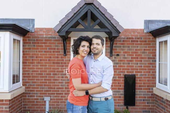 Retrato de pareja feliz frente a su nuevo hogar - foto de stock