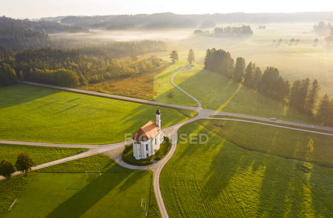 Alemanha, Baviera, Dietramszell, vista aérea dos campos rurais e da Igreja de Saint Leonhard ao amanhecer nebuloso — Fotografia de Stock