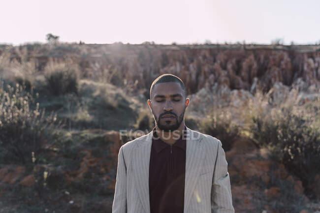 Портрет молодого человека с закрытыми глазами в бесплодной стране — стоковое фото