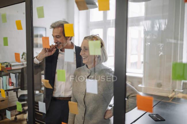Счастливые коллеги смотрят на липкие заметки на стеклянном стекле в офисе — стоковое фото