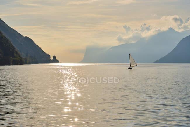 Italy, Trentino, Nago-Torbole, Silhouette of sailboat sailing near coastal cliffs of LakeGardaat moody dawn — Stock Photo