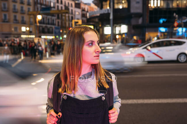 Молода жінка стоїть вночі в місті на вулиці. — стокове фото