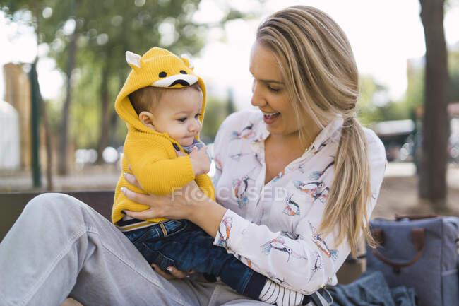 Щаслива мати відпочиває з хлопчиком на лавці в парку. — стокове фото