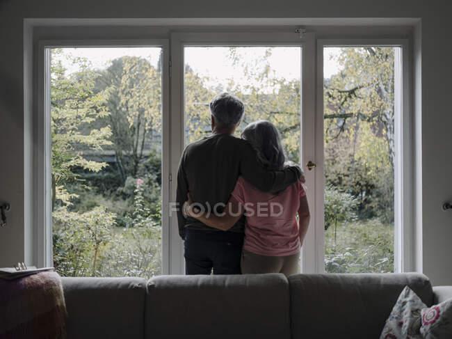 Погляд на старшу пару, яка дивиться у вікно будинку. — стокове фото