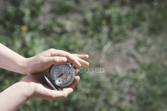 Руки дівчинки тримають срібний кишеньковий годинник. — стокове фото