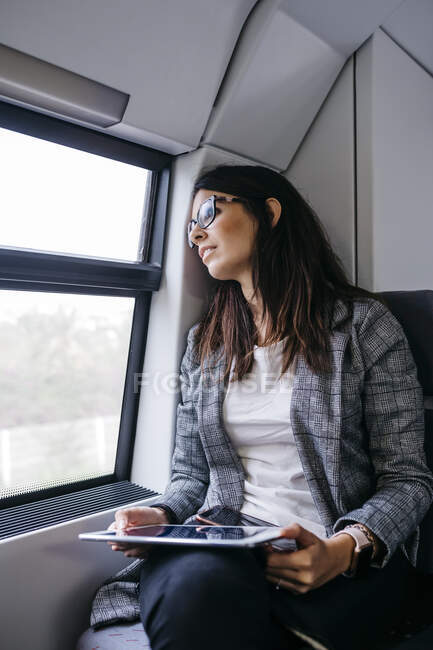 Brunette woman while traveling by train to work, with a tablet in her hands — Stock Photo