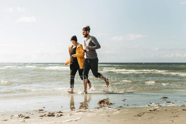 Casal correndo na praia em Heiligenhafen — Fotografia de Stock