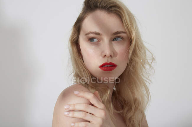 Portrait of young blond woman with red lips and shadow on her face — Stock Photo