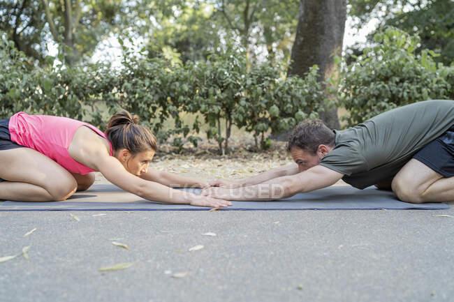 Мужчина и женщина растягиваются на коврике на открытом воздухе — стоковое фото